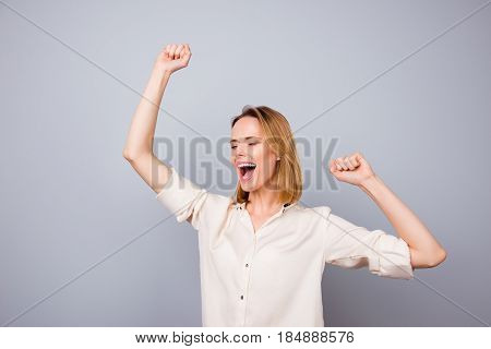 Happy Woman Laughing And Triumphing With Raised Arms Against Gray Background