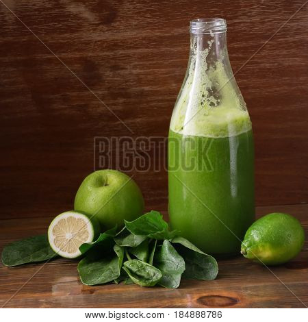 Green fresh pressed juice detox Apple lime and spinach in a glass container. Healthy lifestyle proper nutrition. A dark background and copy space. Selective focus.