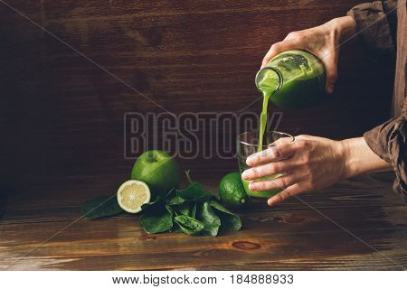 Freshly squeezed juice of green Apple lime and spinach pour into a glass. Healthy lifestyle proper diet detox. A dark background and copy space .Toning.