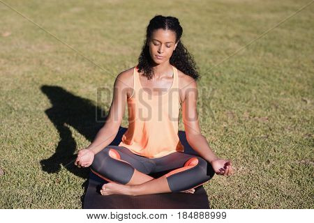 Young woman practicing lotus position on mat at park
