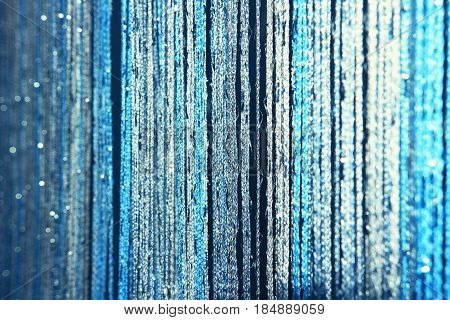 Background texture curtains made of blue threads with glitter and blur at the edges. Fibers of threads of blue curtains sparkle in the light.