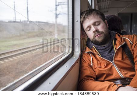 Beautiful young hipster man in an orange jacket asleep near a window in a train