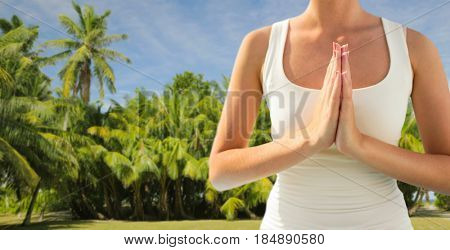 yoga and people concept - close up of woman doing namaste gesture outdoors over exotic natural background with palm trees