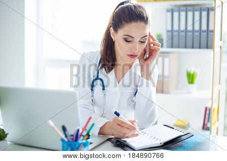Photo Of Smart Young Confident Female Doctor Sitting At The Table Receiving A Call From A Patient An