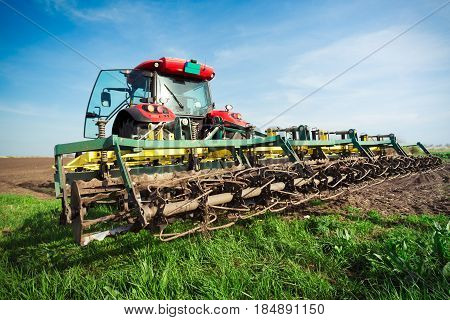 Farmer in tractor preparing land with seedbed cultivator in early spring