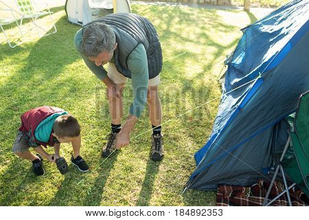 Father and son setting up the tent at campsite