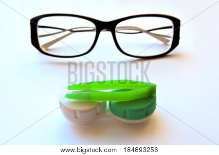eye contact lenses container with green tweezers and eyeglasses on white background.