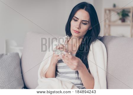 Portrait Of Troubled Ill Young Woman Sitting At Home Holding Glass Of Water And Reading Discription