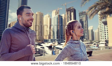 fitness, sport, people, technology and lifestyle concept - happy couple running and listening to music in earphones over dubai city street background
