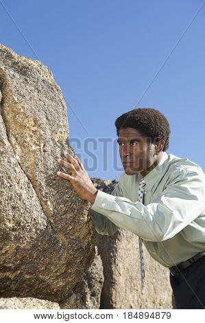 African American businessman pushing rock