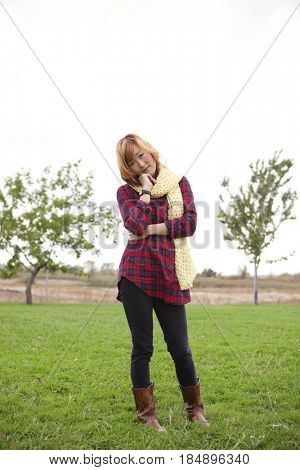 Unhappy Korean woman standing in park