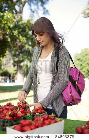 Woman buying strawberries from farmer's market