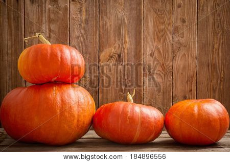 the three pumpkins on old wooden background