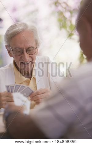 Senior men playing cards outdoors