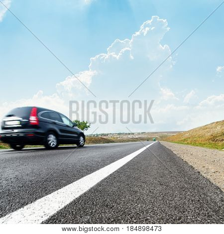 car on road in motion and blue sky with clouds over it