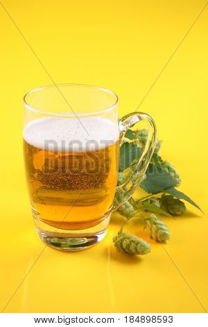 Pint of beer and the twig Hops (Humulus L.) on a yellow background