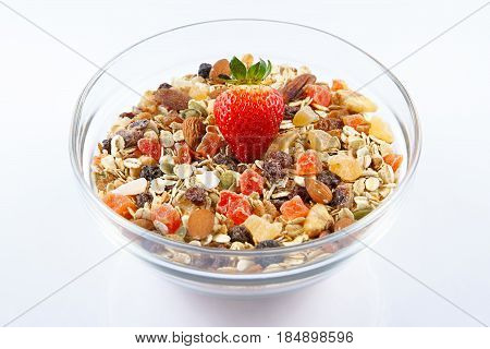 Breakfast cereals and Strawberry oatmeal with strawberry candied fruits raisins and nuts in a glass bowl white background