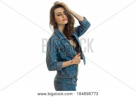 beautiful young girl in denim clothes holding her hand near the hair and looks toward isolated on white background