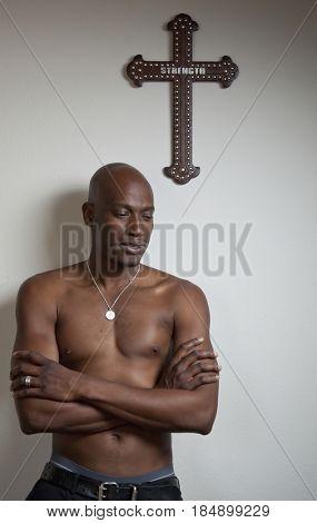 African American man standing underneath cross