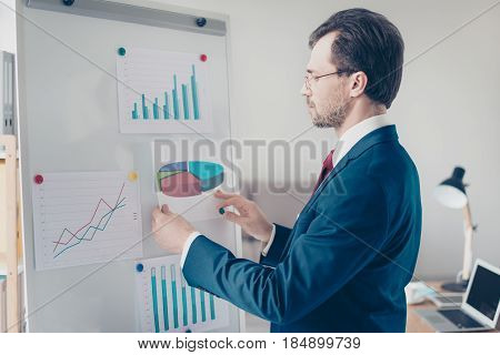 Close Up Side View Of Focused Businessman Putting Paper With Pie Chart On White Board, Reporting The