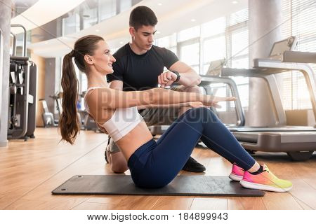 Experienced personal trainer timing and guiding young fit woman during isometric exercise for abdominal muscles in a modern fitness center