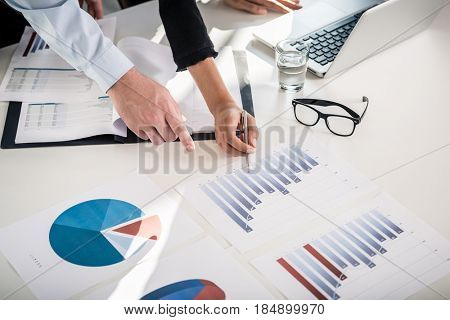 Business experts analyzing statistical information from vertical bar and pie charts printed in the office