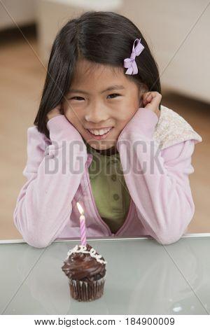 Smiling Korean girl looking at birthday cupcake