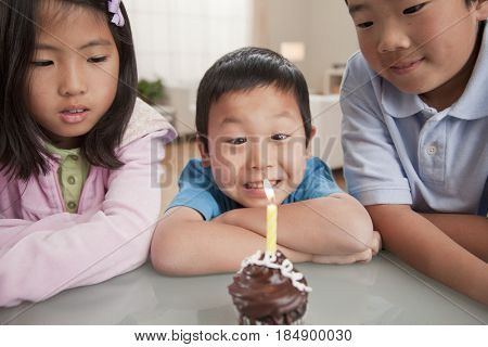 Korean children looking at birthday cupcake
