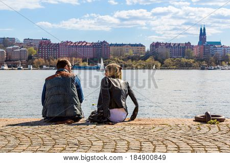 Man and woman on a quay. Stockholm, Sweden - May 01, 2017: Caucasian man and woman sitting close together on a quay in Stockholm. Sunbathing and relaxing with water and buildings in the background.