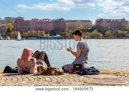 Young woman and dog on a quay. Stockholm, Sweden - May 01, 2017: Two young woman and a dog sitting and laying on a quay in the center of Stockholm, Sweden. Relaxing and sunbathing, water and skyline.