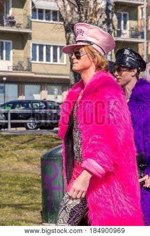 Two men in colorful furs. Stockholm, Sweden - May 01, 2017: Two caucasian men showing off in colorful fake furs and hats walking together in a park in central Stockholm. Background with a blurred man.