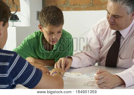 Hispanic father playing dominoes with sons