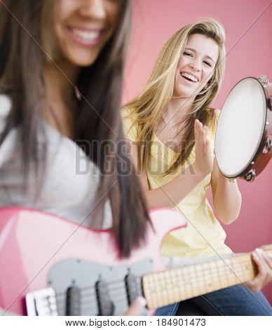 Teenage girls playing guitar and tambourine