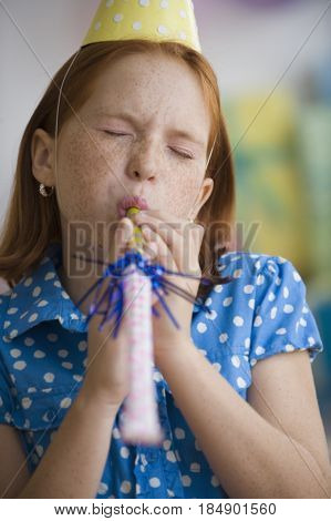 Caucasian girl blowing party noise maker