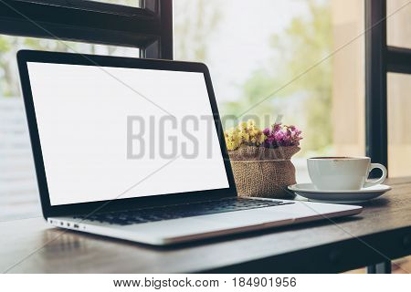 Mockup image of laptop with blank white screen a cup of coffee and flower vase on wooden table in modern loft cafe