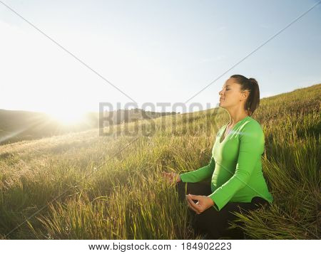 Pregnant Hispanic woman practicing yoga in field