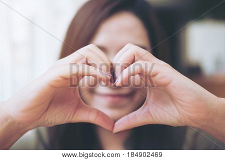 A happy woman making heart hand sign over her face with feeling love