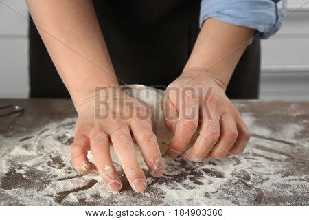 Female chef kneading dough in kitchen