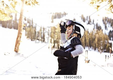 Mixed race boy in helmet having snowball fight