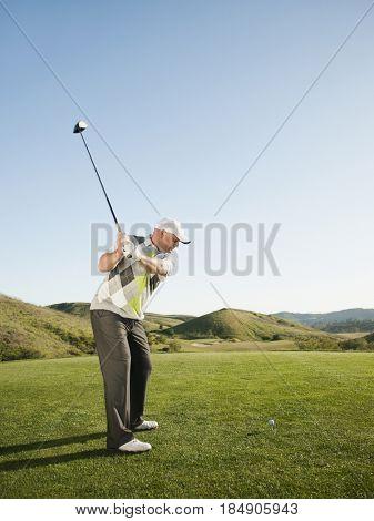 Caucasian golfer preparing to swing golf club