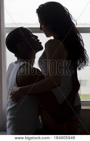 Couple hugging near window