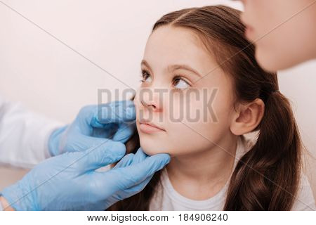 Allergic kid. Excellent smart accomplished dermatologist wearing special gloves for checking childs skin while she sitting at his office