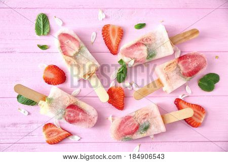 Homemade ice pops with flowers and strawberry on color wooden background