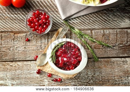 Delicious cranberry sauce in bowl on wooden background, top view