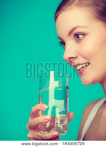 Hydration healthy diet drinking concept. Woman holding and drinking water from a glass studio shot on blue background.