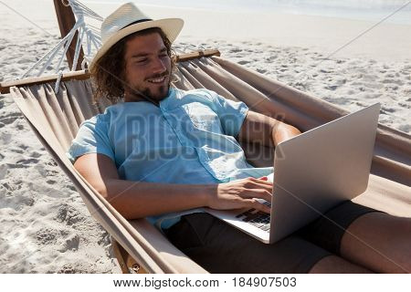 Smiling man relaxing on hammock and using laptop on the beach
