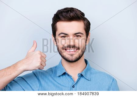 Close Up Portrait Of The Happy Brunet`s Model Face In Jeans Shirt On Lifgt Background Showing Thumb