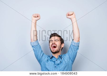Portrait Of Very Excited Young Man, Celebrating Victory With Raised Hands And Screaming