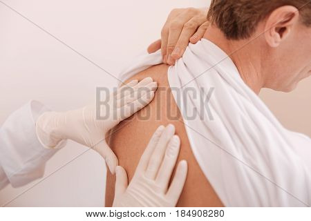 It hurts under shoulder-blade. Mature athletic worried man experiencing some problems with his spine and visiting a specialist while showing her his back