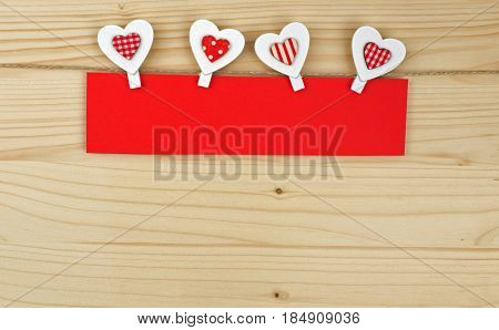 Four hearts with clothes pegs and red paper on a cord on wood